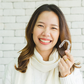 A young adult with a straight smile holding Invisalign